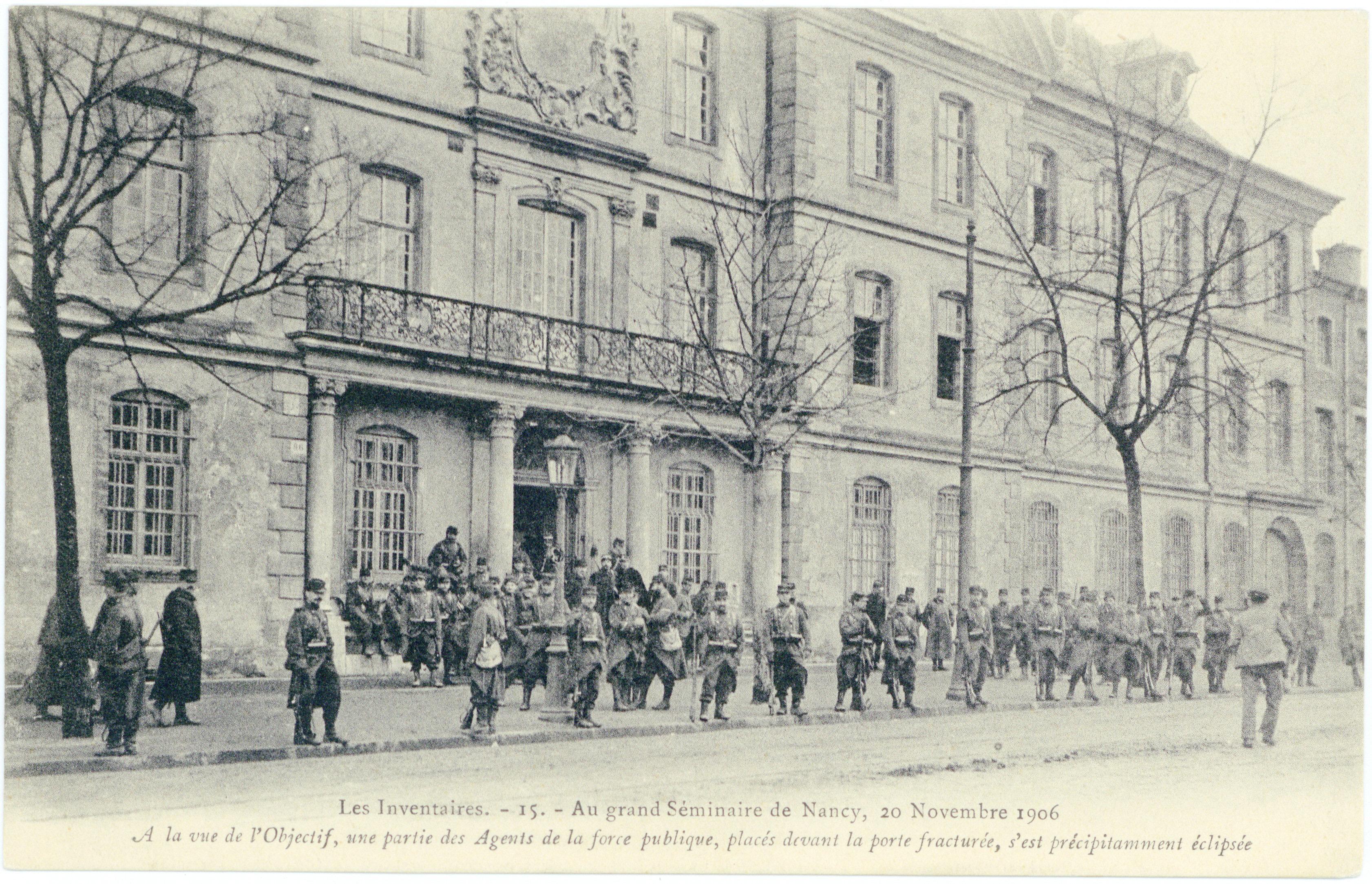 Contenu du Au grand Séminaire de Nancy, 20 novembre 1906 : à la vue de l'objectif, une partie des agents de la force publique, placés devant la porte fracturés, s'est précipitamment éclipsée : les inventaires