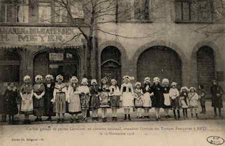 Un joli groupe de petites Lorraines, en costume national, attendant l'arri…
